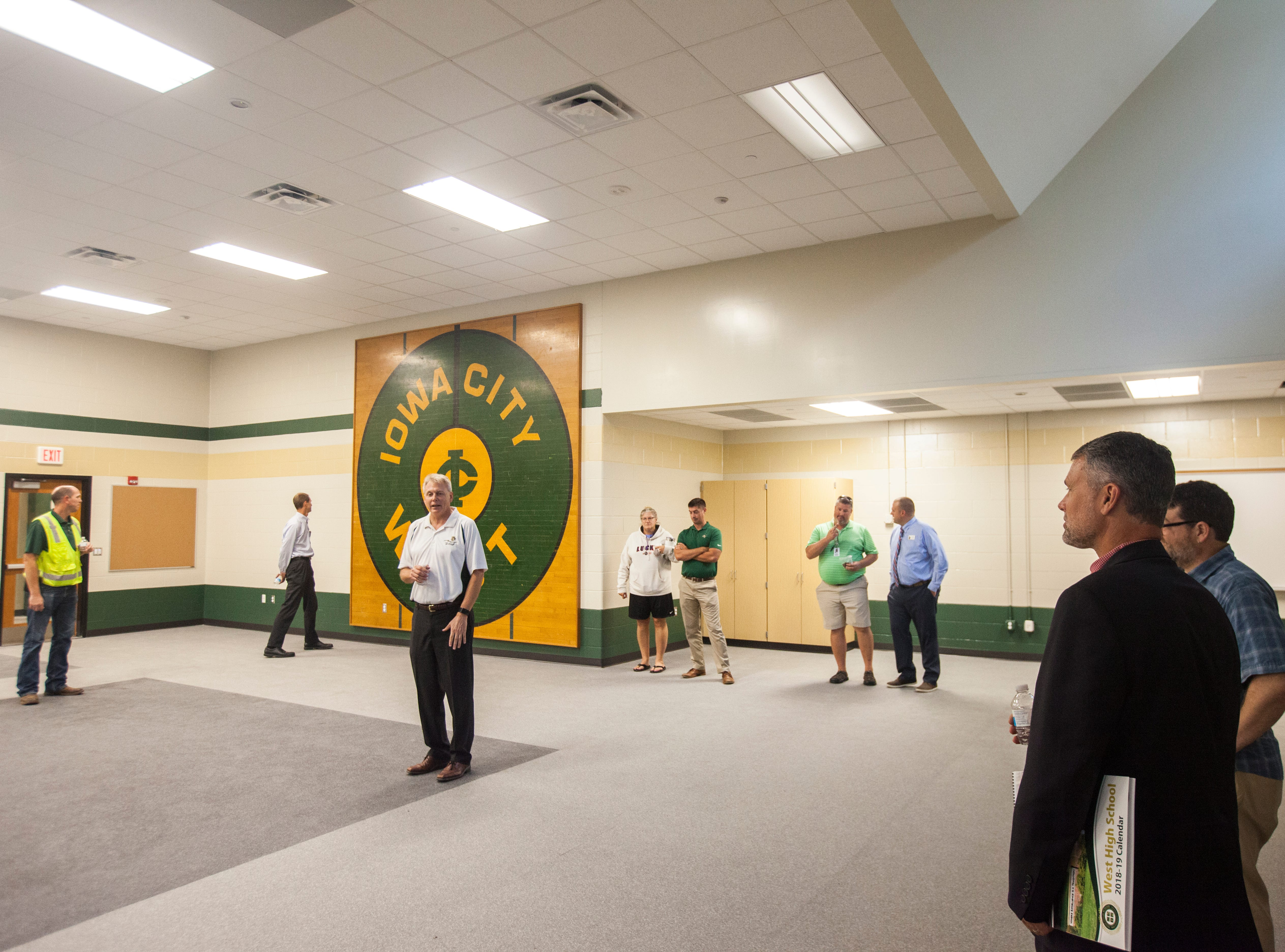 Gregg Shoultz, West High principal, speaks in a weight room during a tour of a recently completed addition to facilities on Wednesday, Aug. 15, 2018, at West High School in Iowa City. The floor from the original gymnasium has been saved and turned into a wall hanging inside the weight room.