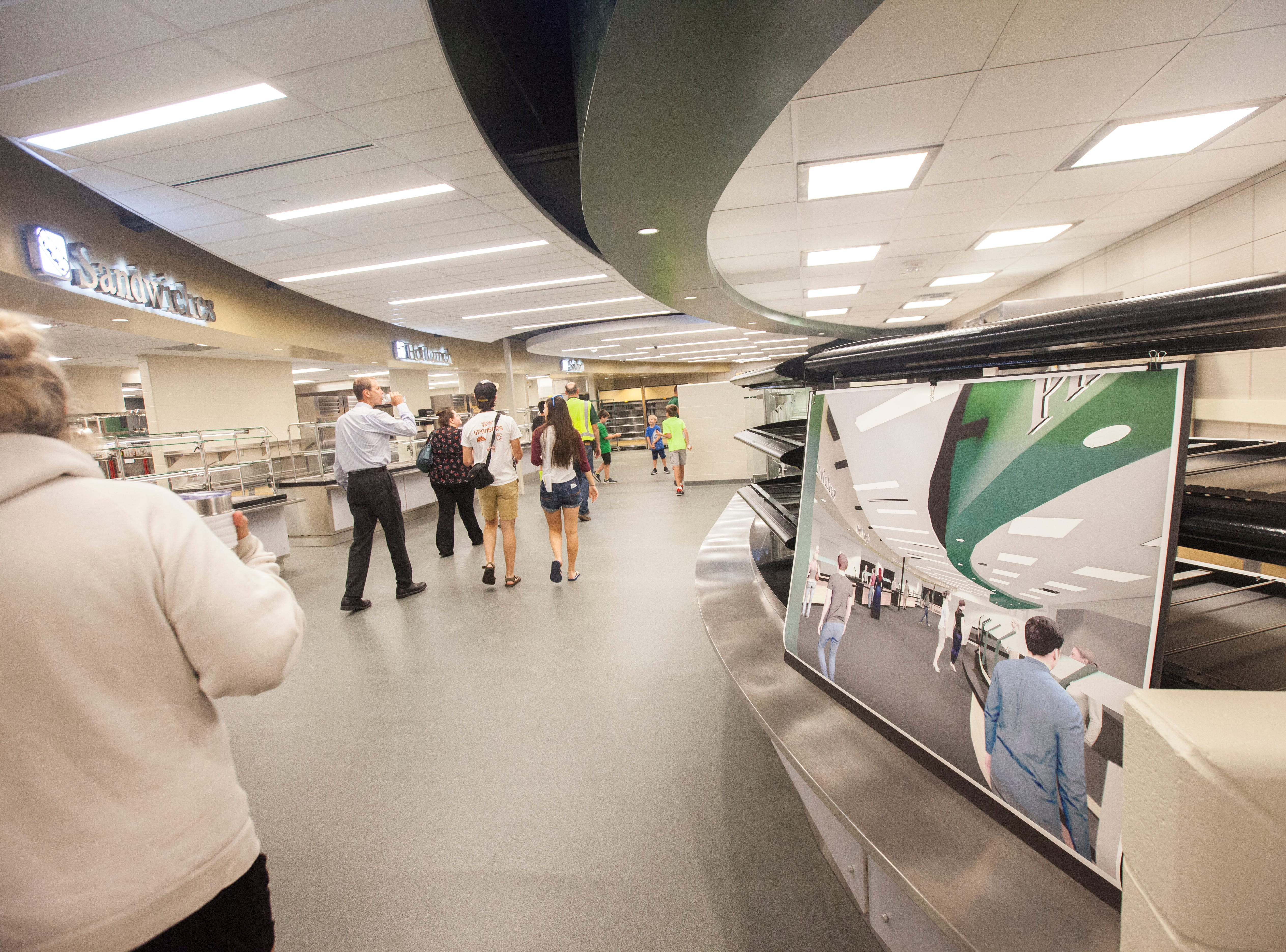 Community members walk through a cafeteria line during a tour of a recently completed addition to facilities on Wednesday, Aug. 15, 2018, at West High School in Iowa City. The addition was the first phase of renovations set to take place for the building that opened in 1968.