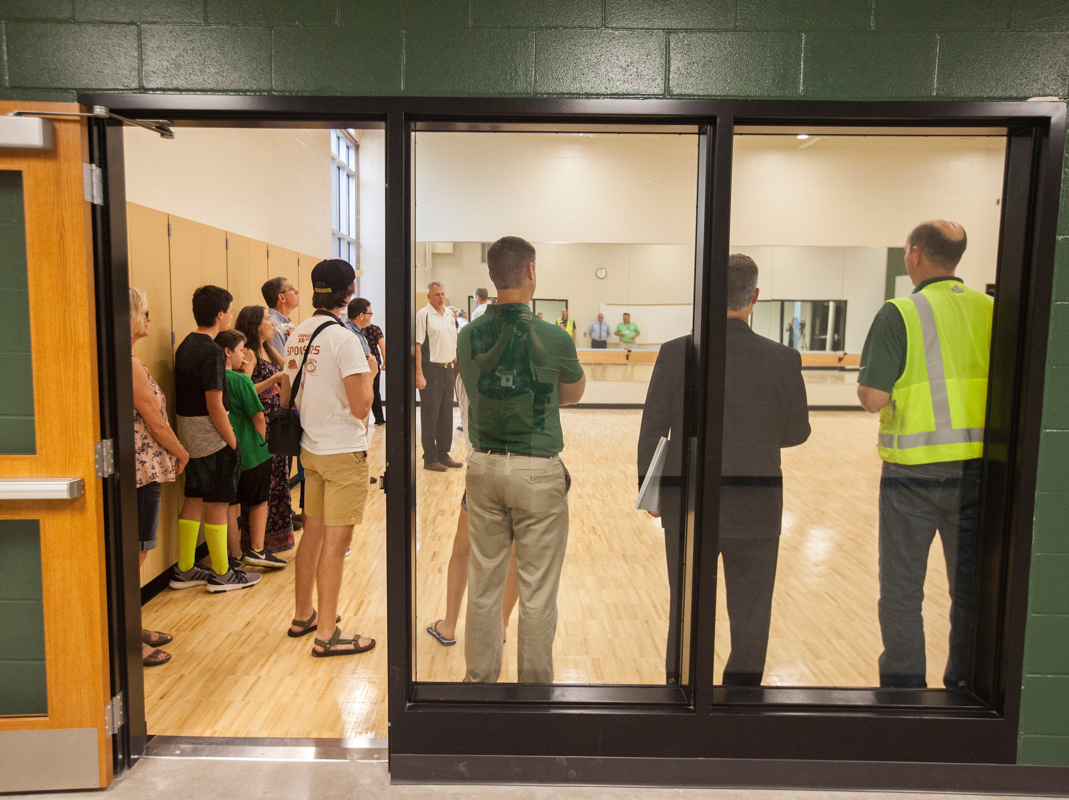 Community members stand in a room for the dance team during a tour of a recently completed addition to facilities on Wednesday, Aug. 15, 2018, at West High School in Iowa City. The addition was the first phase of renovations set to take place for the building that opened in 1968.