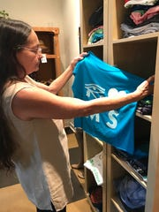 Leslie Puckett, manager of Fair Trade Green in Jackson, looks at one of the T-shirts for sale at the store.