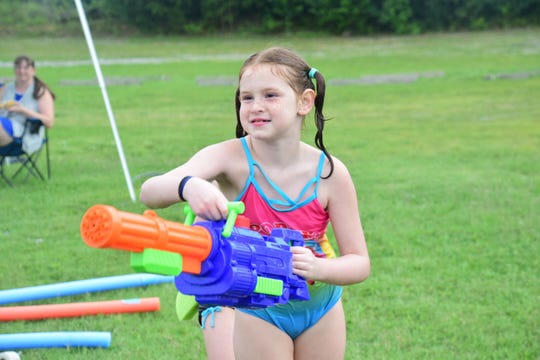 Hannah Fair, 8, takes aim with her Super Soaker at the Aqua Grande Splash Party held at West Town Christian Church Sunday, Aug. 5.