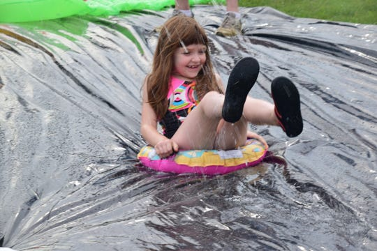 Ariel Allen, 6, tries to gain some traction on her tube during the Aqua Grande Splash Party held at West Town Christian Church Sunday, Aug. 5.
