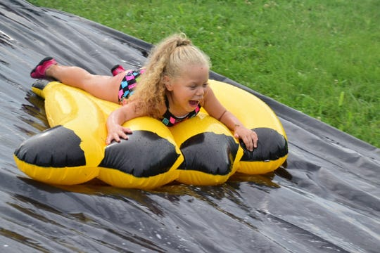 Jailynne Jones, 4, flies down the wet hill on a raft at the Aqua Grande Splash Party held at West Towne Christian Church Sunday, Aug 5.