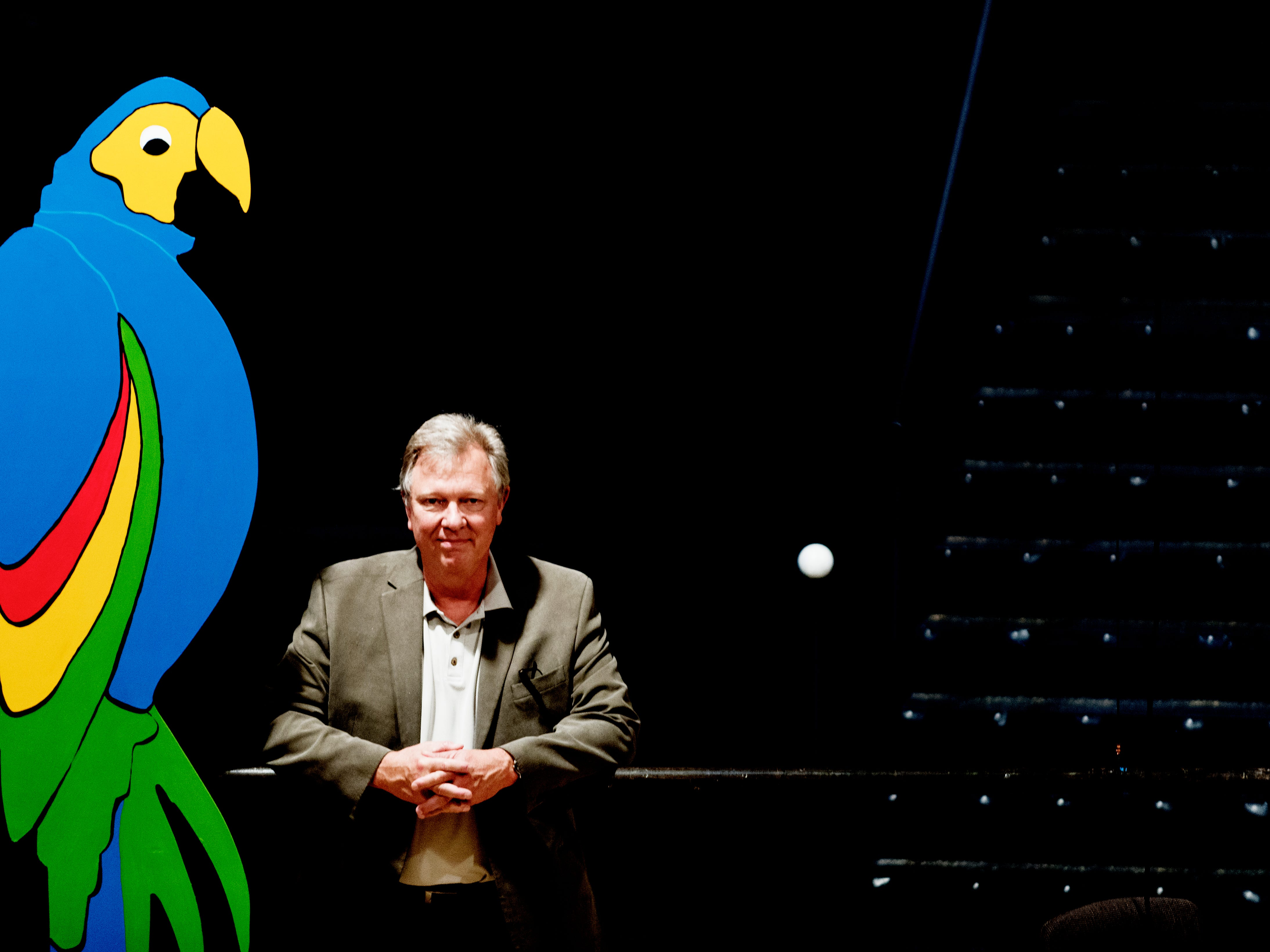 "Calvin MacLean, director of Candide, poses beside a parrot figure ahead of opening day for ""Candide"" at the Clarence Brown Theatre in Knoxville, Tennessee on Tuesday, August 14, 2018. Leonard Bernstein's acclaimed operetta, ""Candide,"" is to open Friday, Aug. 31, with previews beginning Aug. 29."