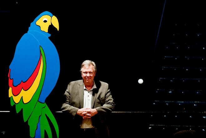"Calvin MacLean, director of ""Candide,"" poses beside a parrot figure ahead of opening day for ""Candide"" at the Clarence Brown Theatre in Knoxville on Aug. 14. Leonard Bernstein's acclaimed operetta, ""Candide,"" will open Friday, Aug. 31, with previews beginning Aug. 29."