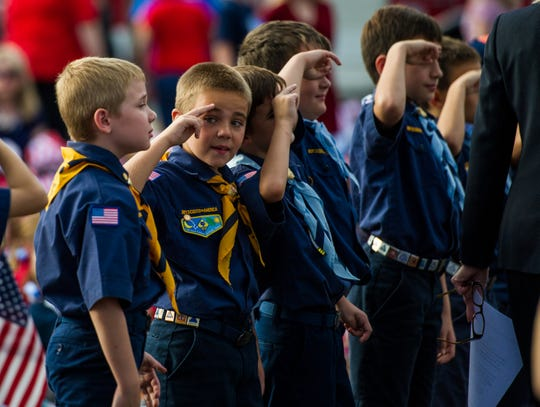 A group of Cub Scouts raise their hands in salute during a Veterans Day celebration at Woodvalle Elementary School in Lafayette, La., Wednesday, Nov. 11, 2015.
