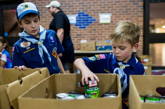 Cub Scouts Noah Weaver, 8, and Everett Hillman, 9, sort food while volunteering for FoodNet's annual Food for Families food drive at the Cajundome in Lafayette, La., Tuesday, Dec. 8, 2015.