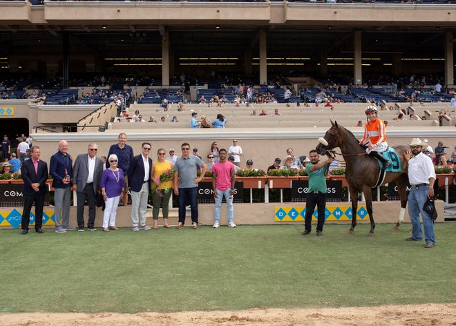 Party Dancer, the horse Rick Pitino (sixth from left in jacket) co-owns, is pictured in the winner's circle at  Del Mar Thoroughbred Club on Aug. 9.