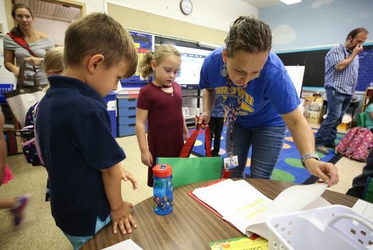 Kindergarten teacher Jennifer Funk works to get all of the students in the right classrooms on Wednesday morning at J. Graham Brown School on the first day of classes at JCPS.