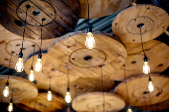 A detailed look at the large light fixture made out of repurposed wood spools at Cask & Company restaurant and bar on Tuesday, Aug. 14, 2018, in Lansing. The business, formerly Xiao, has gone under a complete renovation including the addition of 30 60-inch TVs for the sports bar crowd.