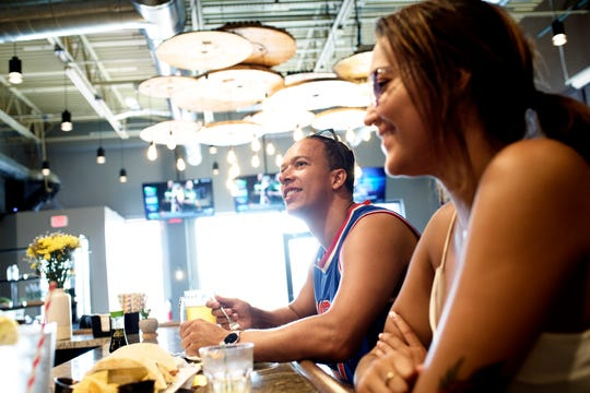 Patrons Michael Morgan, left, and Bianca Cavazos enjoys lunch while seated at the bar on Tuesday, Aug. 14, 2018, at Cask & Company restaurant and bar in Lansing. The business, formerly Xiao, has gone under a complete renovation including the addition of 30 60-inch TVs for the sports bar crowd.
