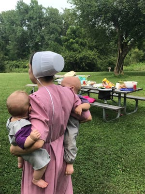 Gloria holds baby Elijah and Jesse at a picnic.