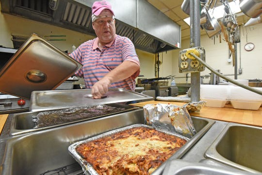 Russ Kent is hard at work Tuesday night as he serves lasagna to his customers at the American Legion in Galion. Kent serves a hot meal made from scratch every Tuesday at the downtown Galion hall.