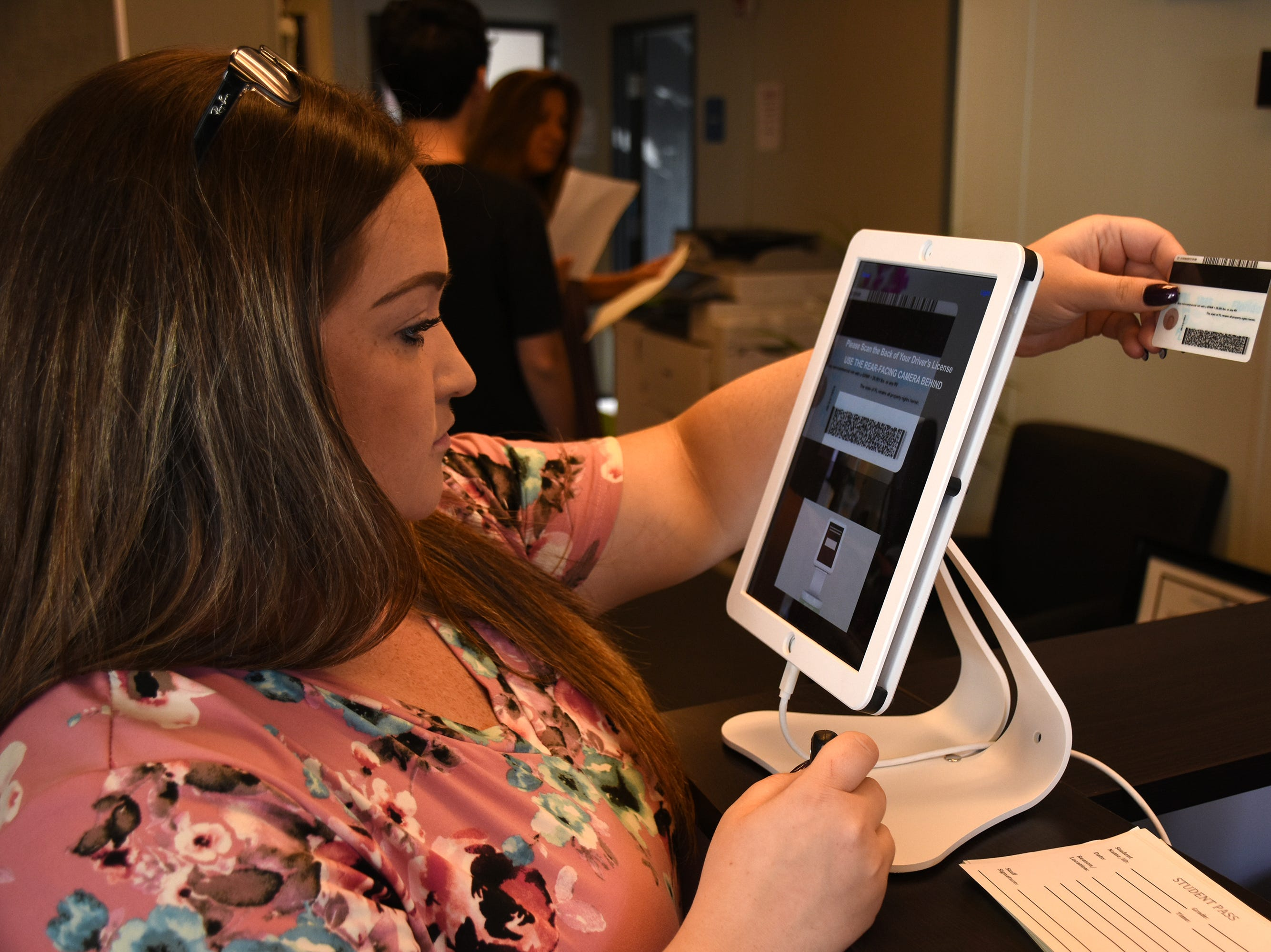 School secretary Meagan Carr scans a visitor's ID at Marco Island Academy. Marco Island students, along with all of Collier County, returned to school for the first day of classes in the new school year on Wednesday.