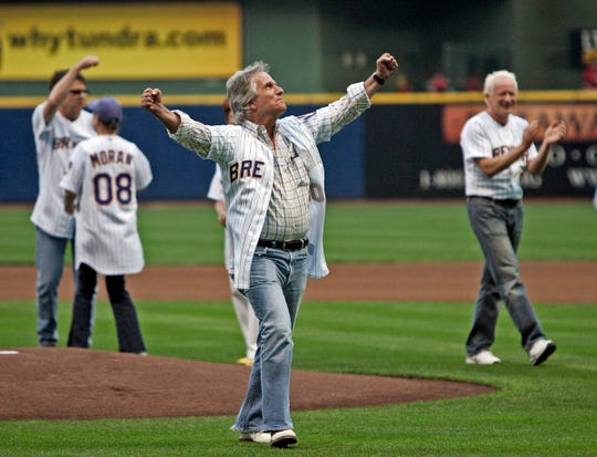 Henry Winkler raises his arms after throwing out the first pitch before game between the Milwaukee Brewers and Houston Astros at Miller Park Tuesday, August 19, 2008.