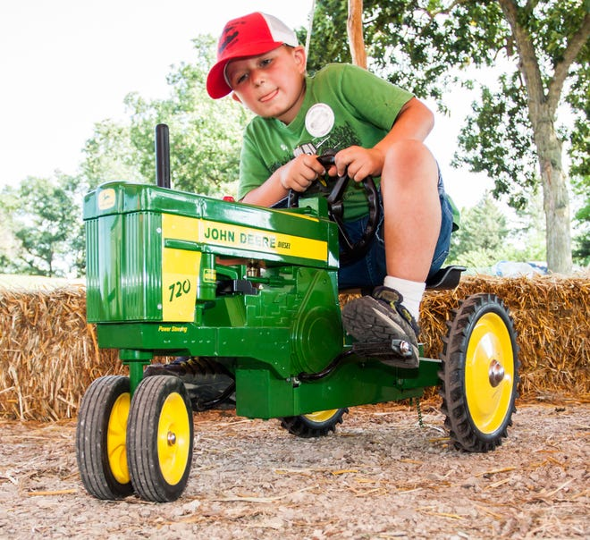 Ian Cera of Sussex enjoys a ride on one of several pedal-powered tractors in the children's tent during a past annual Antique Power Show at Sussex Village Park.