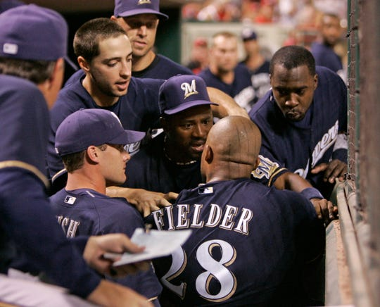 Milwaukee Brewers' Prince Fielder (28) is held back by his teammates after he had an altercation with starting pitcher Manny Parra in the dugout during a baseball game against the Cincinnati Reds, Monday, Aug. 4, 2008, in Cincinnati.