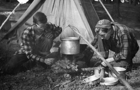A pair of attendees at Camp Manito-wish YMCA build a campfire in this photo from the 1940s.