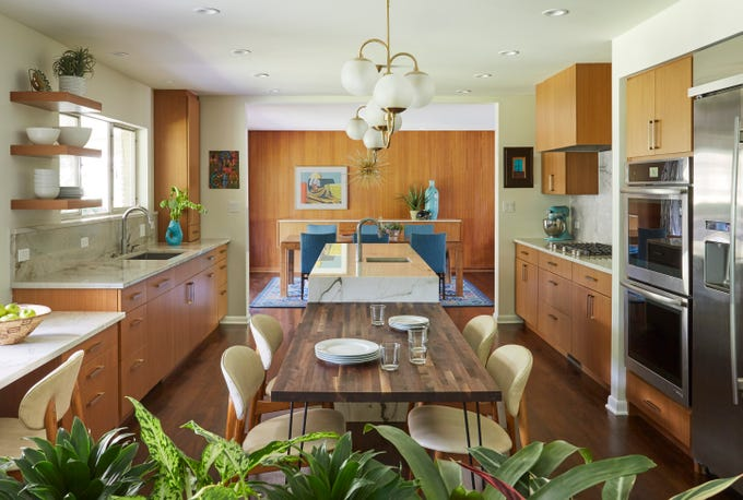The island in this mid-century modern Chicago home has a teak veneer and quartzite top, leading to a lower level kitchen table. (KitchenLab Design)