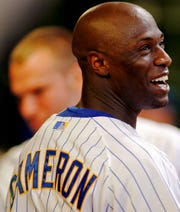 Milwaukee Brewers' Mike Cameron smiles in the dugout after hitting a two run home run against the Pittsburgh Pirates in the seventh inning of a baseball game Friday, Aug. 22, 2008, in Milwaukee.