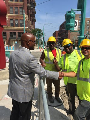 Earnell Lucas, winner of Tuesday's Democratic primary for Milwaukee County sheriff, is greeted by a city public works crew working on lighting for The Hop MKE streetcar line on St. Paul Ave.