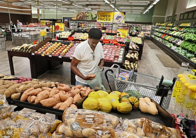 Henry Davis of Milwaukee selects sweet potatoes at the Pick 'n Save Midtown Center. A ribbon-cutting ceremony was held to celebrate the store's $2 million remodeling by Roundy's.