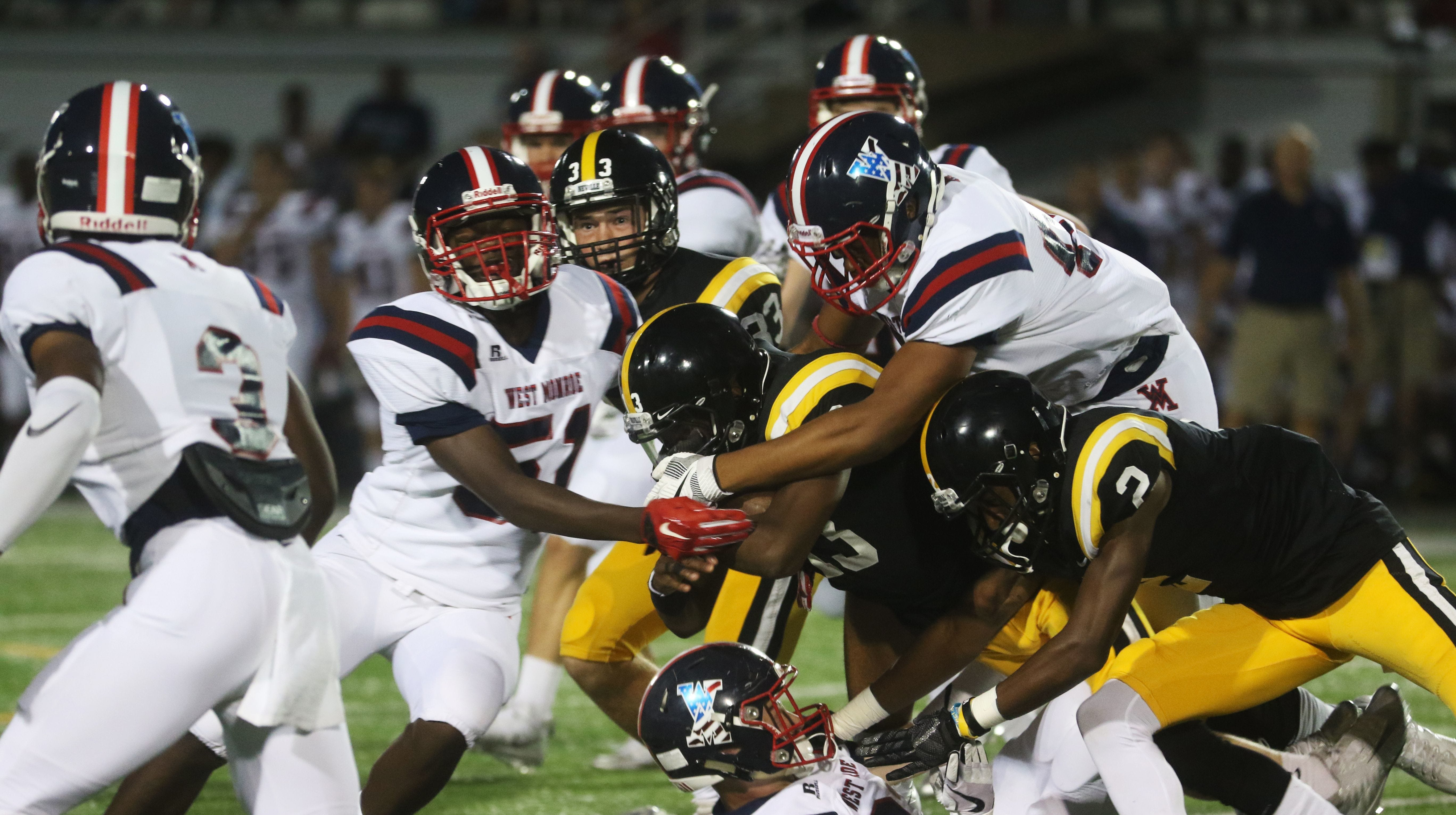 The West Monroe defense tackles a Neville ball carrier during the 2017 game between the teams.