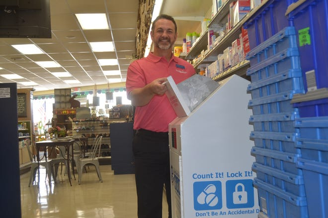 Perkins Drugs owner and pharmacist Andrew Finney demonstrates the new permanent Count It! Lock It! Drop It! prescription drug drop-off box.