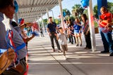 Community and faculty members greet students as they arrive for the first day of school at Mike Davis Elementary.