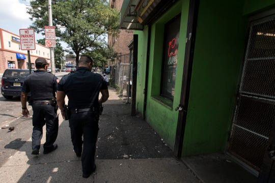 """Paterson Police officers Eric Marino and Joshua Serrano walk on Broadway in Paterson on Wednesday, August 15, 2018. In response to the latest wave of public complaints about the plague of lawlessness in the area, police launched a new """"park-and-walk"""" operation near the city's main library."""