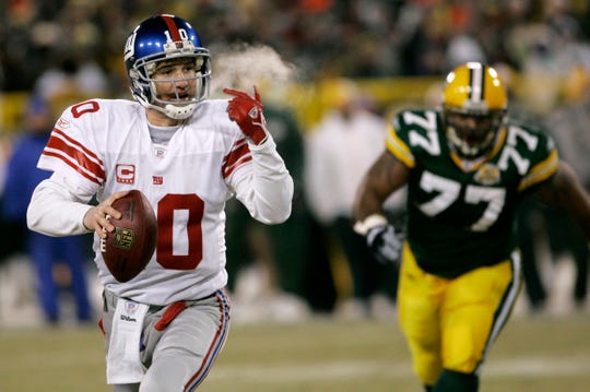 New York Giants quarterback Eli Manning looks to throw a pass as he runs from Green Bay Packers defensive end Cullen Jenkins (77) during the NFC Championship football game, Sunday, Jan. 20, 2008, in Green Bay, Wis. (AP Photo/David Duprey)