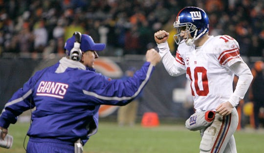 New York Giants quarterback Eli Manning, right, and head coach Tom Coughlin celebrate as officials confirm teammate Amani Toomer's fourth-quarter touchdown catch during a football game against the Chicago Bears, Sunday, Dec. 2, 2007 in Chicago. The Giants defeated the Bears, 21-16. (AP Photo/M. Spencer Green)
