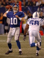 In this September 10, 2006, Giants Eli Manning (10) passing before being hit by the Colts Gary Brackett (58) Sunday night at Giants Stadium in East Rutherford.