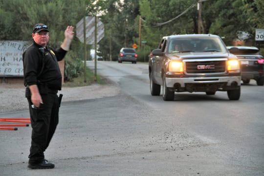 A New Mexico State Police officer directs traffic at Alamo Street and La Luz Road Tuesday afternoon.
