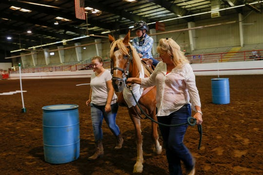 Nathanael Muller rides Savvy around barrels Wednesday during an equestrian show at the San Juan County Fair in Memorial Coliseum at McGee Park in Farmington.