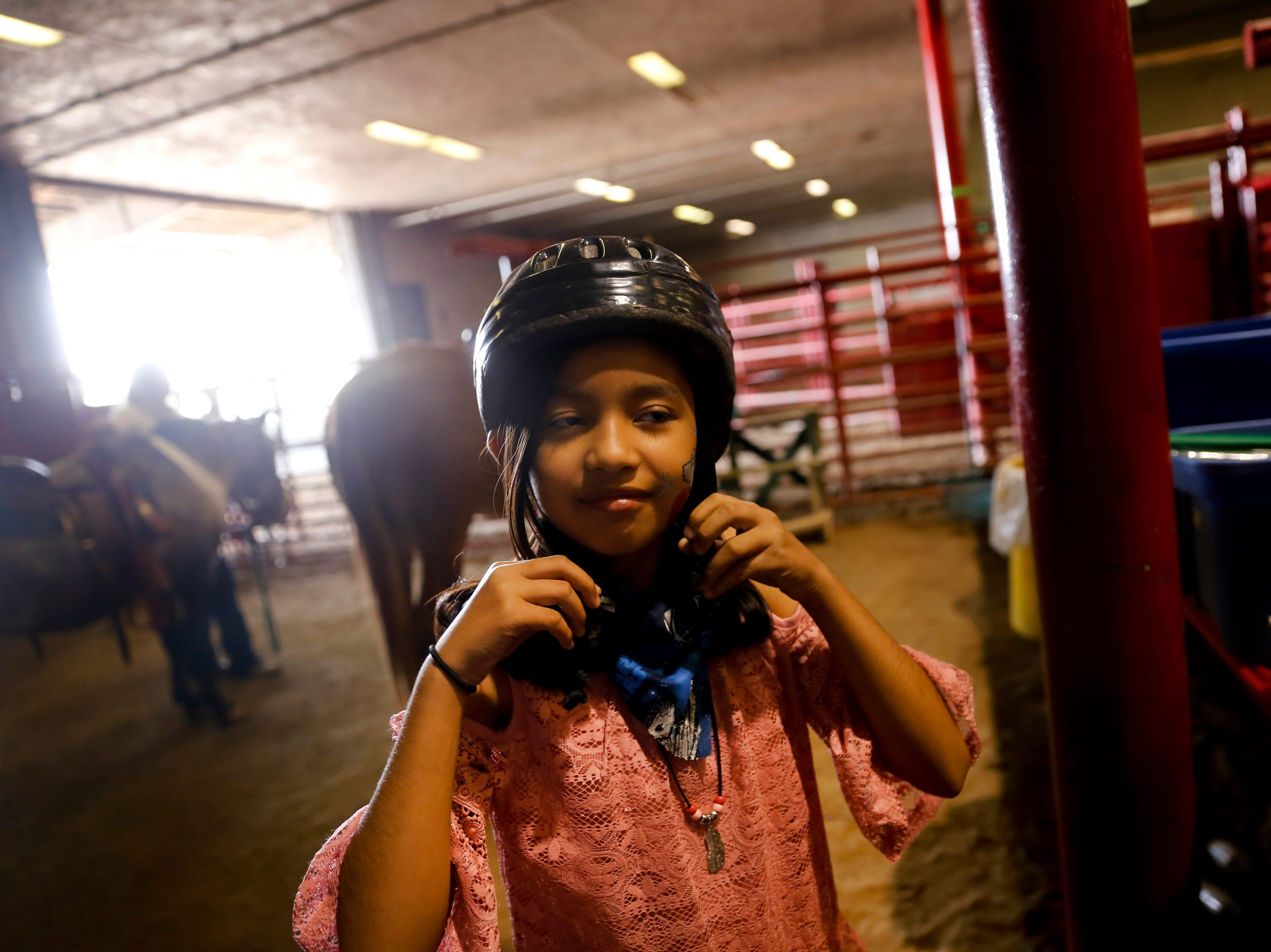 Kyana Perez, puts on her helmet, Wednesday, Aug. 15. 2018 during an equestrian show for people with  disabilities at the San Juan County Fair in Memorial Coliseum at McGee Park in Farmington