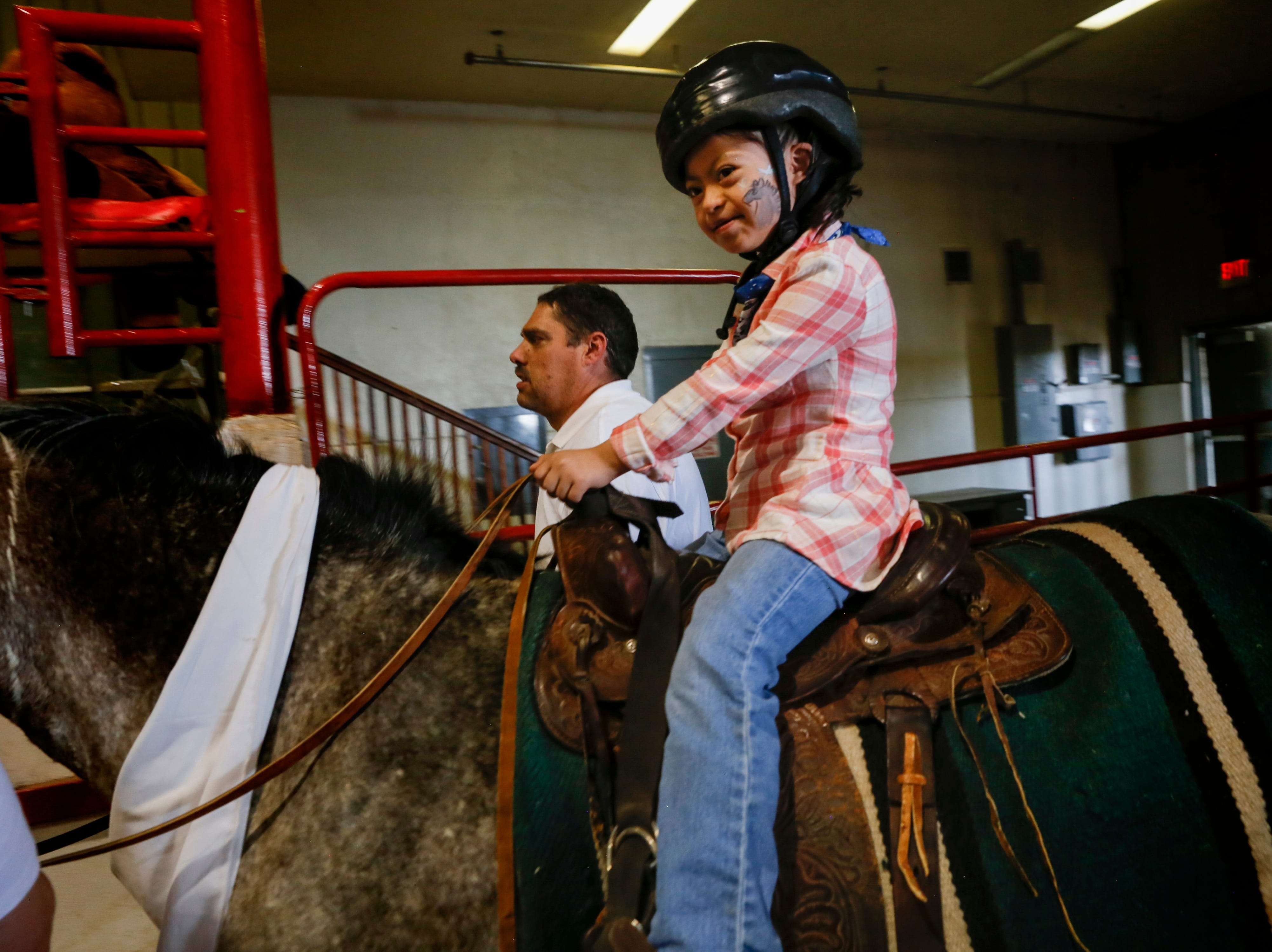 Dyanna Perez is led out of the arena on top of Chiple, Wednesday, Aug. 15. 2018 for an equestrian show for people with disabilities at the San Juan County Fair in Memorial Coliseum at McGee Park in Farmington
