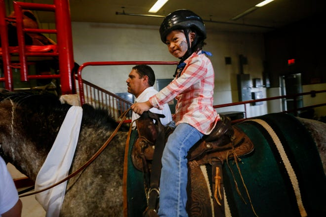 Dyanna Perez is led out of the arena on top of Chiple Wednesday for an equestrian show for people with disabilities at the San Juan County Fair in Memorial Coliseum at McGee Park in Farmington