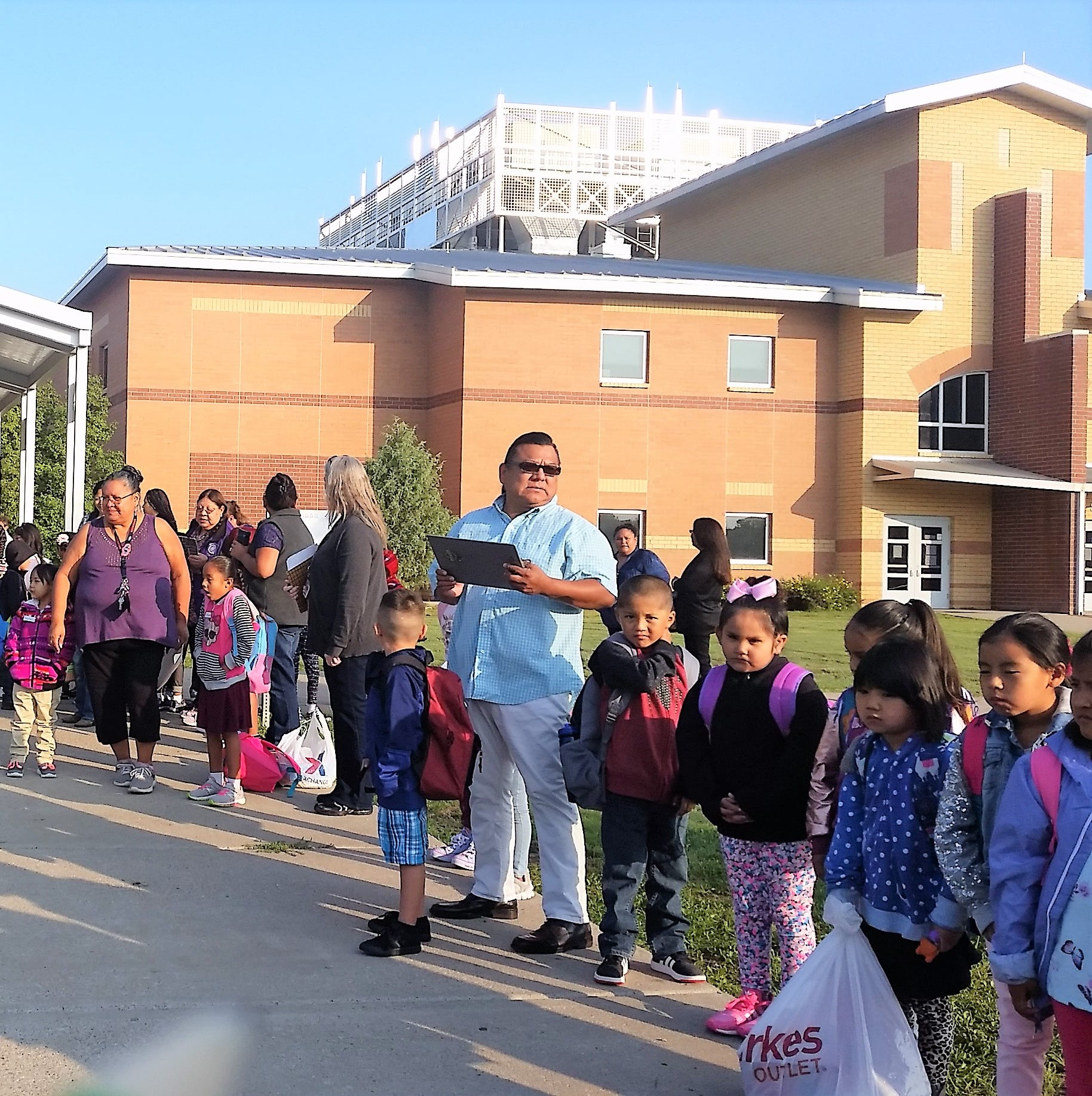 Mescalero Apache students are greeted by teachers as they head back to school