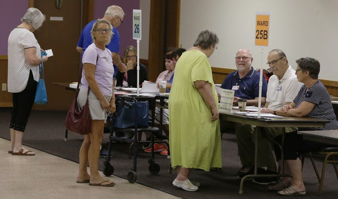 Oshkosh residents get their ballots from poll workers Tuesday, Aug. 14, 2018, during the fall primary election at the Elks Lodge, which handles Wards 25A, 25B and 26.