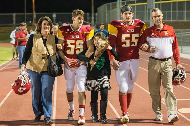 Will Emmett, 55, walks with his family prior to the Senior Night game in 2015.