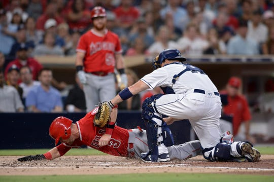 Los Angeles Angels' Taylor Ward (3) is tagged out at home by San Diego Padres catcher A.J. Ellis on a fielders choice hit by Jaime Barria during the second inning of a baseball game Tuesday, Aug. 14, 2018, in San Diego. (AP Photo/Orlando Ramirez)
