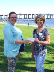Emerald Coast Woman's Club President Dorothy Hayes, right, presents a check to Michelle Abrams for the Weekend Food Program, which provides backpacks of food for needy children in the Navarre area.