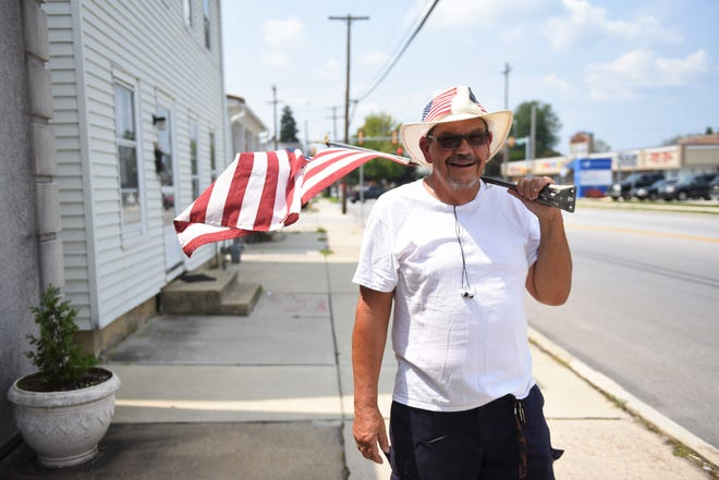 Mike Grey walking down York Street with his American flag flying proud on Aug. 15.