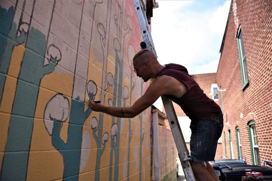 Chris Lower, a director of Waldo's & Company and designer of the mural, is seen painting around the brains of the 'brain forest,' on Aug. 13, 2018.