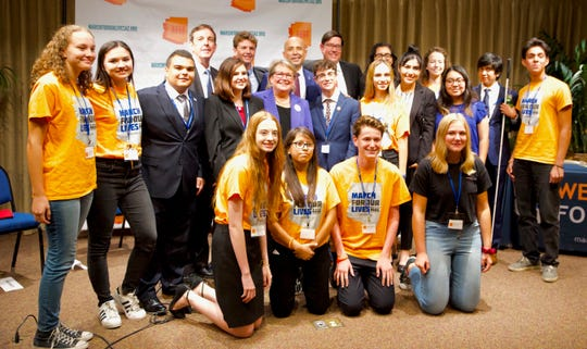 Gubernatorial candidates pose with student activists from March for Our Lives Arizona, which hosted a town hall on gun-control issues. Incumbent Gov. Doug Ducey did not attend.