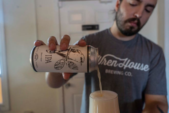 Luke Wortendyke, opens a can of Rain Crow IPA beer, named after the western yellow-billed cuckoo's more common name, at Wren House Brewing Company in Phoenix.