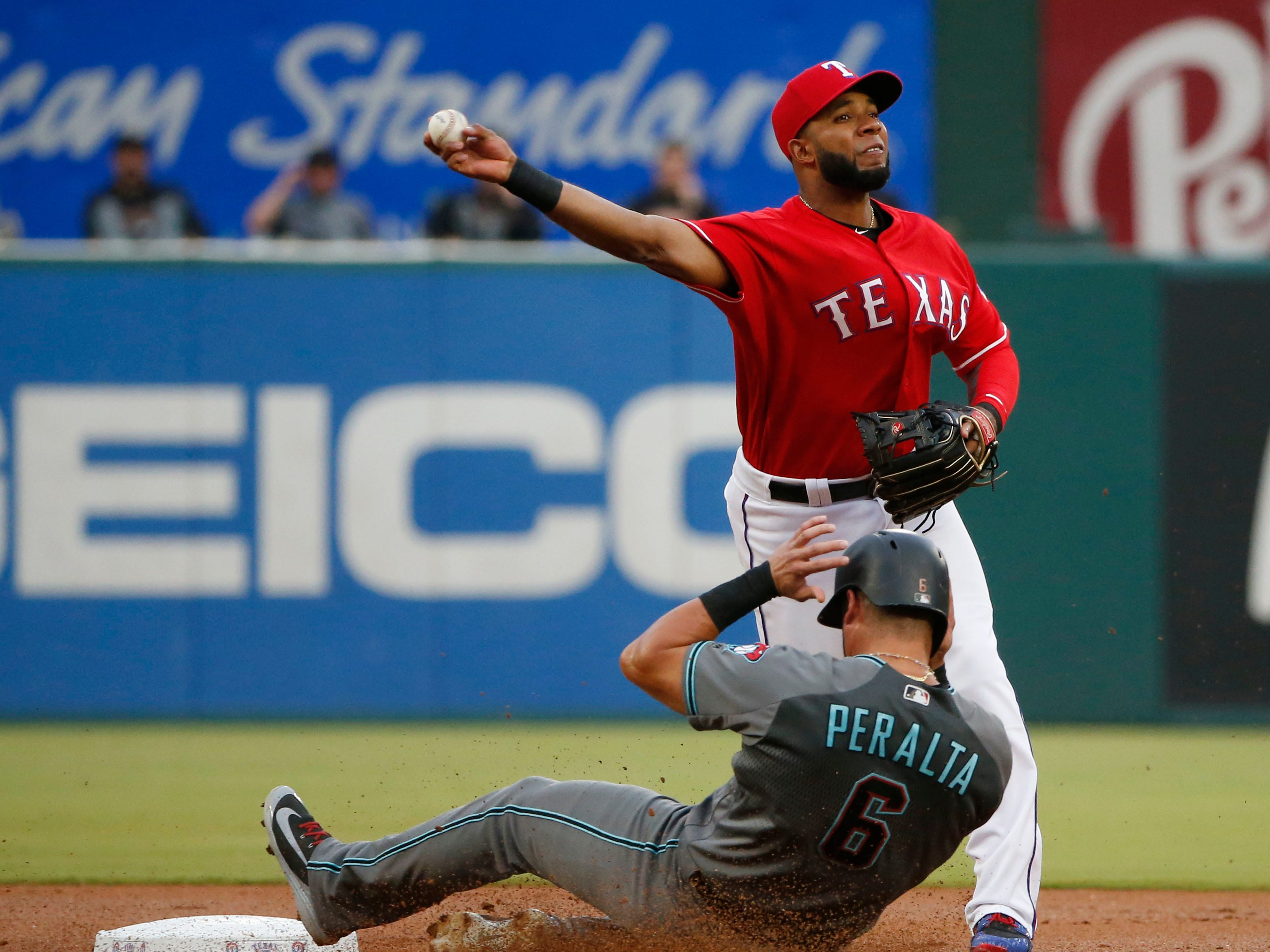 Arizona Diamondbacks' David Peralta (6) is forced out by Texas Rangers shortstop Elvis Andrus (1) for a double play that ended the first inning of a baseball game Tuesday, Aug. 14, 2018, in Arlington, Texas.