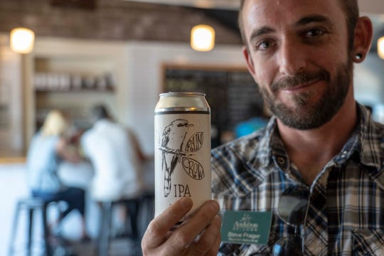 Steven Prager, Audubon Arizona important bird area program associate holds a can of the Rain Crow IPA beer at Wren House Brewing Company in Phoenix.