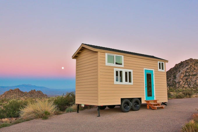 A view of a tiny home with an Arizona sunset in the background.